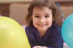 Petite fille mignonne de sourire se trouvant sur le lit avec des ballons Image stock