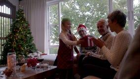 Petite fille mignonne donnant le cadeau de Noël à sa grand-mère clips vidéos