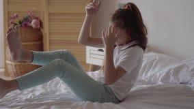 Petite fille mignonne drôle avec des écouteurs écoutant la musique sur le lit Jeune mélomane ayant l'amusement avec la musique à  banque de vidéos