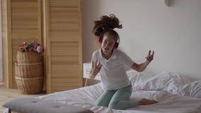 Petite fille mignonne drôle mettant sur des écouteurs et essayant de danser et tombant sur le lit Jeune mélomane ayant l'amusemen clips vidéos