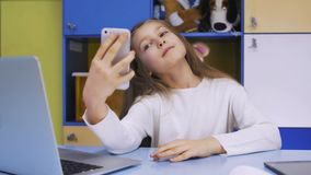 Petite fille mignonne employant Smartphone moderne Photographie stock