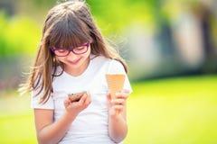 Petite fille mignonne en parc un jour ensoleillé avec la crème glacée et le téléphone portable  Photo stock