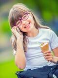 Petite fille mignonne en parc un jour ensoleillé avec la crème glacée et le téléphone portable  Photos stock
