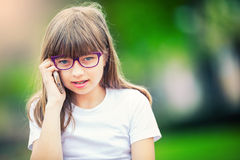 Petite fille mignonne en parc un jour ensoleillé avec la crème glacée et le téléphone portable  Image libre de droits