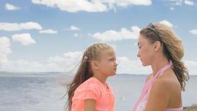 Petite fille mignonne et jeune mère à la plage photos stock