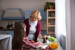 Petite fille mignonne et sa grand-mère faisant cuire dans la cuisine Image libre de droits