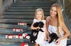 Petite fille mignonne et sa mère étreignant des chiots de chien Photographie stock