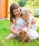Petite fille mignonne et sa mère étreignant des chiots de chien Image stock