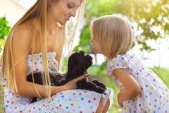 Petite fille mignonne et sa mère étreignant des chiots de chien Photographie stock libre de droits