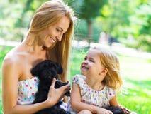 Petite fille mignonne et sa mère étreignant des chiots de chien Photo stock