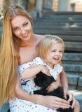 Petite fille mignonne et sa mère étreignant des chiots de chien Photos stock