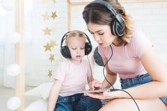 Petite fille mignonne et sa maman écoutant la musique sur des écouteurs à la maison images libres de droits