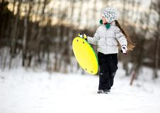 Petite fille mignonne exécutant dans la neige avec la soucoupe Photos libres de droits