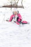 Petite fille mignonne gambadant dans la neige Image stock