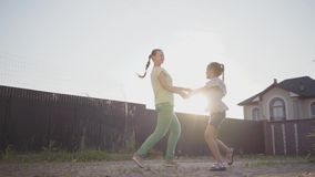 Petite fille mignonne heureuse et sa mère tournant tenir autour des mains dans l'arrière-cour La femme et l'enfant ayant l'amusem clips vidéos