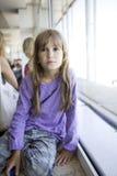 Petite fille mignonne huit années se reposant sur l'hublot Images stock