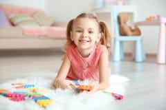 Petite fille mignonne jouant avec des pazzles photos stock