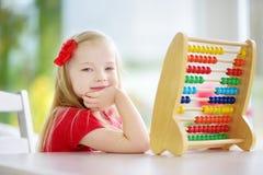 Petite fille mignonne jouant avec l'abaque à la maison Enfant futé apprenant à compter Photos libres de droits
