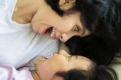 Petite fille mignonne jouant avec sa mère Image stock