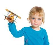 Petite fille mignonne jouant avec un avion de jouet Photographie stock