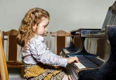Petite fille mignonne jouant le piano à queue à l'école de musique Image libre de droits
