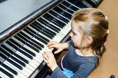 Petite fille mignonne jouant le piano à queue Photographie stock