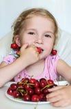 Petite fille mignonne mangeant des cerises Photo libre de droits