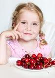 Petite fille mignonne mangeant des cerises Images stock