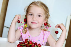 Petite fille mignonne mangeant des cerises Images libres de droits