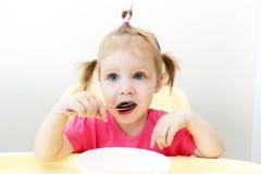 Petite fille mignonne mangeant la cuisine de soupe à la maison photos stock