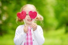 Petite fille mignonne mangeant la lucette en forme de coeur énorme dehors le beau jour d'été Photographie stock libre de droits