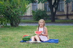 Petite fille mignonne mangeant la pastèque sur l'herbe dans l'heure d'été avec de longs cheveux de queue de cheval et sourire too Photos stock