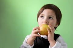 Petite fille mignonne mangeant la pomme Photographie stock