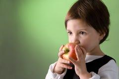Petite fille mignonne mangeant la pomme Image libre de droits