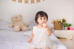 Petite fille mignonne mangeant le biscuit à la maison images libres de droits