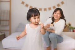 Petite fille mignonne mangeant le biscuit à la maison photo stock