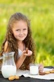 Petite fille mignonne mangeant le gâteau aux pépites de chocolat sur le fond vert images libres de droits