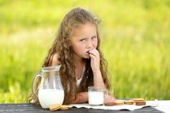 Petite fille mignonne mangeant le gâteau aux pépites de chocolat sur le fond vert images stock