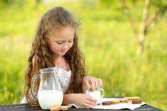 Petite fille mignonne mangeant le gâteau aux pépites de chocolat sur le fond vert image stock