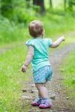 Petite fille mignonne marchant loin sur la route en avant Photos stock