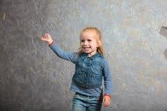 Petite fille mignonne ondulant sa main et posant à l'appareil-photo Photo libre de droits