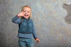 Petite fille mignonne ondulant sa main et posant à l'appareil-photo Image libre de droits