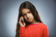 Petite fille mignonne parlant du téléphone portable D'isolement sur le gris photographie stock libre de droits