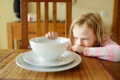 Petite fille mignonne peu disposée à manger de sa soupe Enfant dînant à la maison photographie stock libre de droits