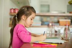 Petite fille mignonne, photo de dessin avec des crayons à la maison image libre de droits