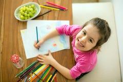 Petite fille mignonne, photo de dessin avec des crayons à la maison images stock
