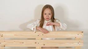 Petite fille mignonne posant dans le studio à côté d'un banc en bois sur le fond blanc banque de vidéos