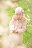 Petite fille mignonne près d'un arbre fleurissant images libres de droits