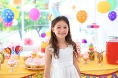 Petite fille mignonne près de table avec des festins à la fête d'anniversaire images stock