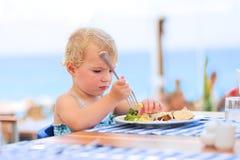 Petite fille mignonne prenant le déjeuner dans le restaurant de station de vacances photos libres de droits